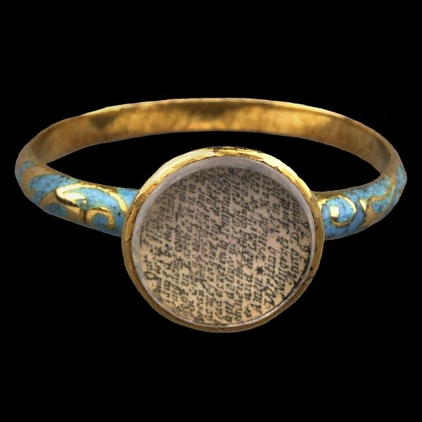 Finger-ring set with the Lord's Prayer. England, AD 1676.  This gold ring contains a miniature version of the Lord's Prayer of the Christian faith, written by hand on a tiny disc of paper, less than a centimetre in diameter and set beneath a faceted sliver of rock-crystal.