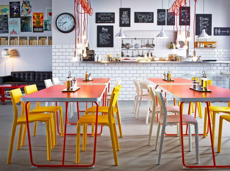 Restaurante com mesas em laranja combinadas com cadeiras em amarelo e branco. Eu colocaria cores mais fortes, o ambiente está muito asséptico...mas a idéia é boa,