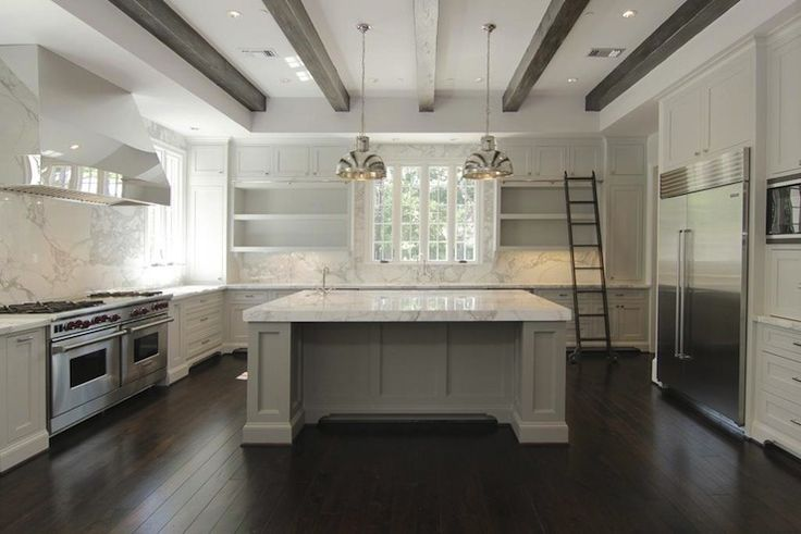 two-tone kitchen with gray kitchen island, crisp white kitchen cabinets, marble countertops, walnut ladder, espresso stained box beams & hardwood floors, sink in kitchen island and polished nickel kitchen hood & pendants.