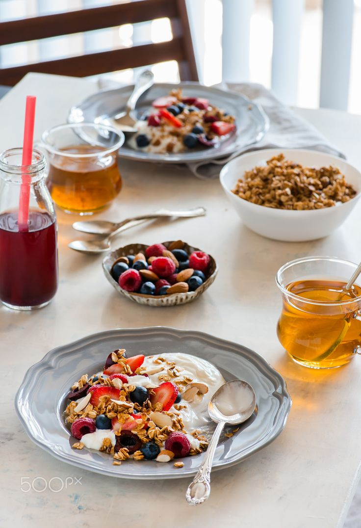 Breakfast with yogurt and granola - Healthy breakfast with greek yogurt, fresh berries and granola. Served for two, window on the background