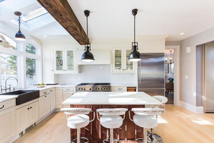 Contemporary kitchen with white cabinets black farmhouse sink, exposed beam & wood island