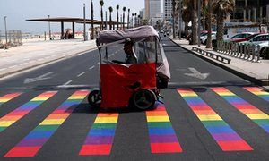 People cross a rainbow-coloured pedestrian crossing before the Tel Aviv gay…