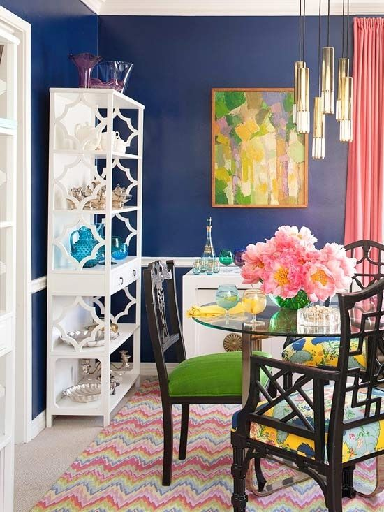 Hollywood regency colourful dining room, gold pendant light, white bookcase & bamboo chippendale chair