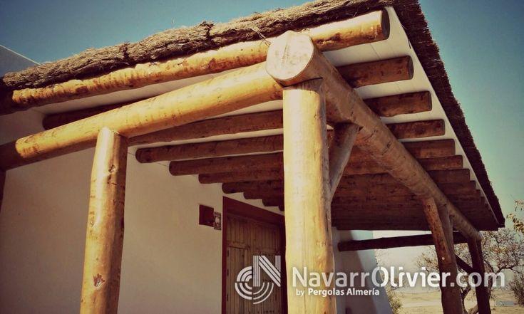 Pérgola adosada de casa rural construida con troncos naturales sin tornear y cubierta de brezo
