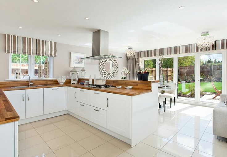 The Winchester by Bovis Homes 2015. Interior Designed Kitchen / living / Dining room using wood work surfaces and white Hamptons style units with a neutral scheme. This house is beautifully designed, the bi - folds featured here mirror the ones in the living room.