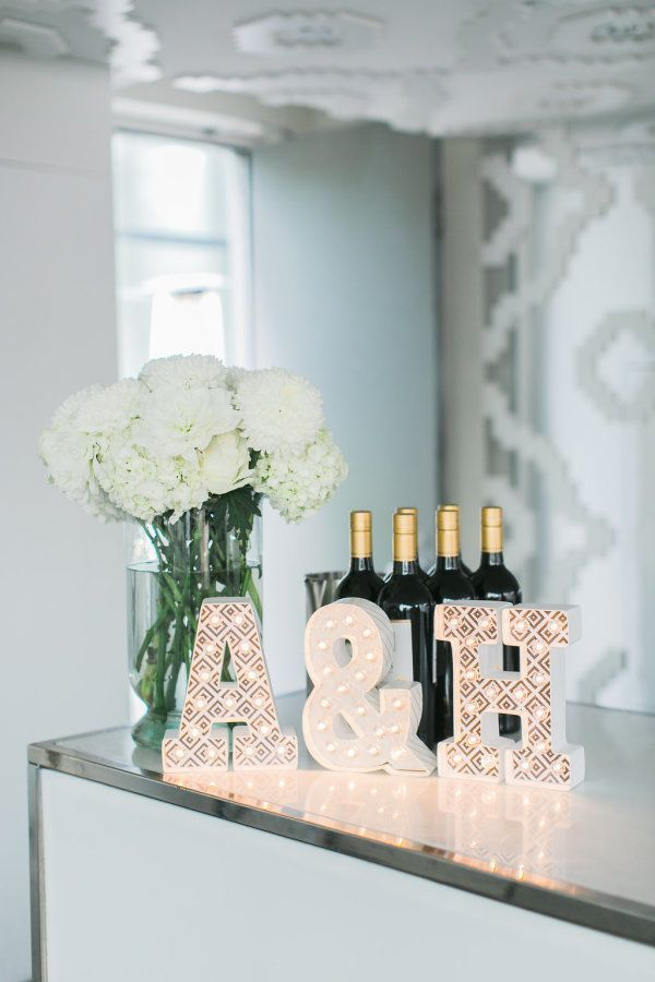 The celebration is ready to begin with these beautiful white hydrangeas, newlywed initials, and wine! http://www.stylemepretty.com/canada-weddings/ontario/toronto/2016/08/11/romantic-rooftop-wedding-at-malaparte/ Photography: Rhythm - http://rhythm-photography.com/