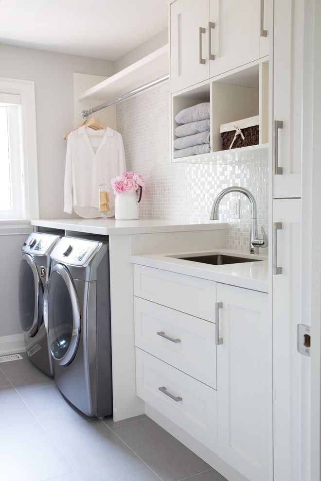 Small laundry room, glass mosaic backsplash, white cabinets, grey floor tiles. Ample space - organised and functional!
