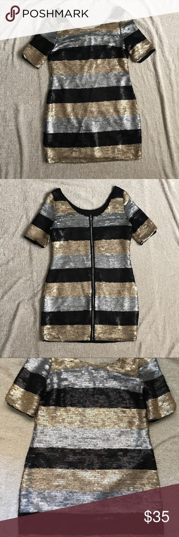 Shimmer gold, black, and silver dress Zip front down the whole back. This is a very unique and fun dress. Block gold, black, and silver stripes running horizontally. Runs big, I would suggest ordering a size smaller than you'd normally get. Dresses