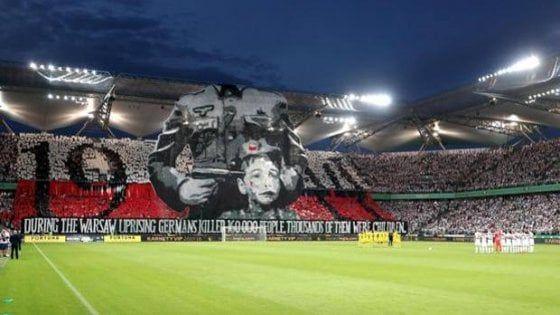 I tifosi polacchi hanno esibito un enorme striscione con un soldato delle SS senza volto che punta una pistola alla tempia di un bambino per ricordare la