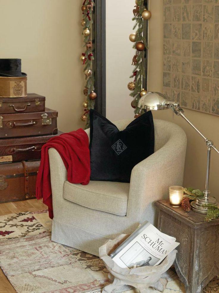 Kunstig granbar henger rundt dørkarmen, pyntet med julekuler og røde sløyfer. Gamle kofferter er plassert oppå hverandre på gulvet ved siden av den lille lesekroken. Styling: Tone Kroken.