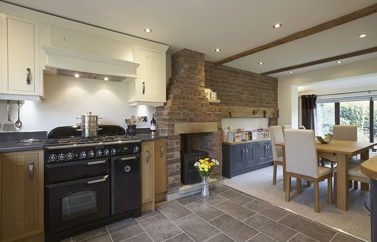 This traditional kitchen in Bradford retained a nostalgic warmth with its original exposed brick fireplace and contrasting light painted cabinets