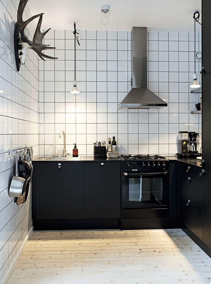 Scandinavian kitchen with industrial touch. black cabinets, white tiles and black grout