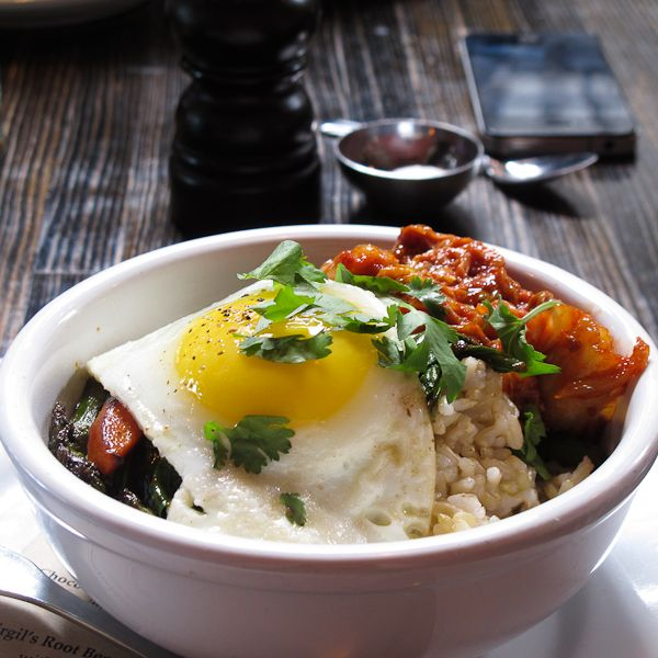 John's Breakfast, a sunny-side up egg served over brown rice with kim chee and vegetables (asparagus, spinach and carrots)