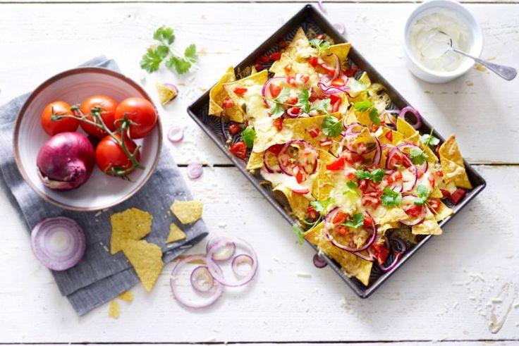 Onweerstaanbare borrelhap: nachos uit de oven met een laag gesmolten kaas - Recept - Allerhande