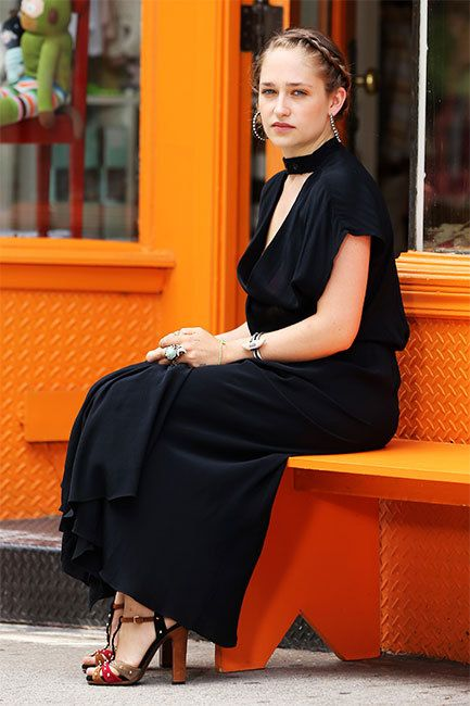 Actress Jemima Kirke sat outside of Le Petit Chapelais in Soho in New York wearing a black wrap dress in between takes of HBO's Girls on June 28th. In character as Girls's Jessa, Kirke worked a braided bun and lots of jewelry to style her look.
