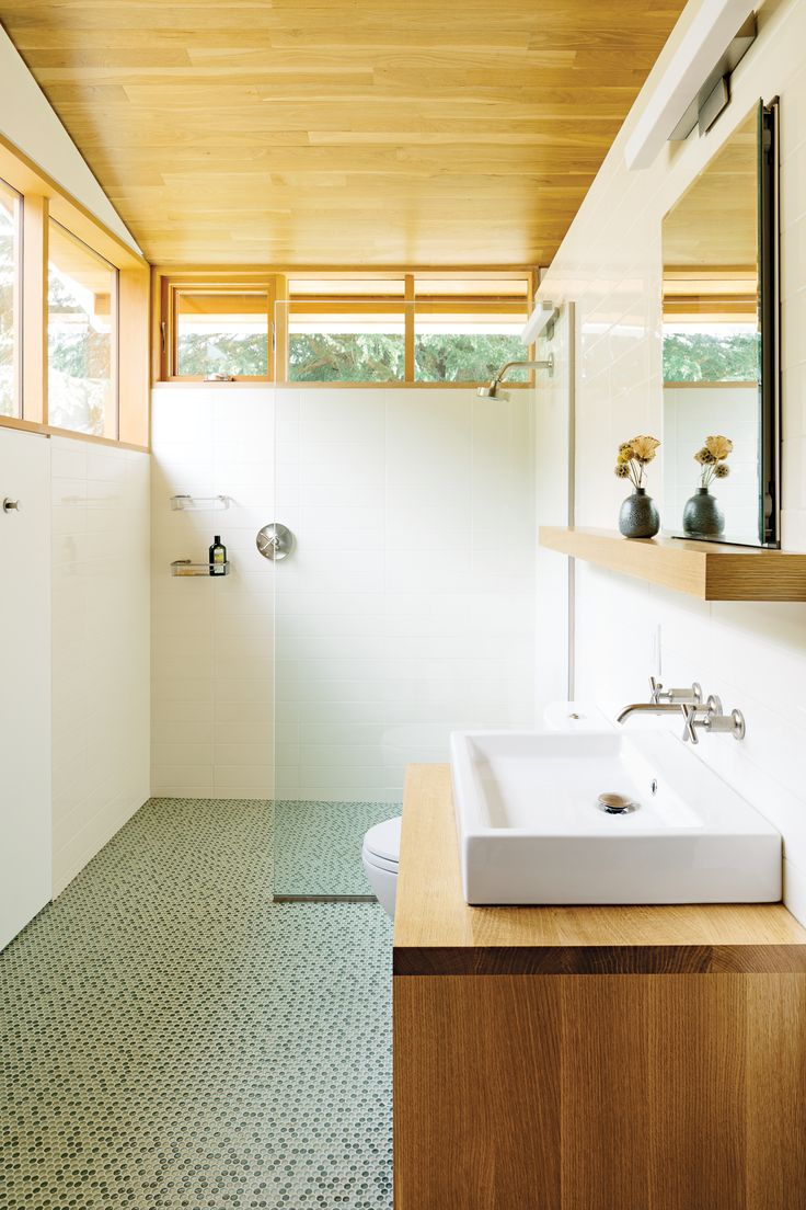 In the bathroom, a thin pane of glass separates the shower; an Aquaplane sink by Lacava hovers above a built-in vanity illuminated by a lean Adelphi light by Oxygen Lighting; and blue-green glass penny tiles by Terra Verre decorate the floor. The absence of a door, combined with windows on two sides, makes the bathroom feel like a continuation of the overall space.  Photo by Lincoln Barbour.