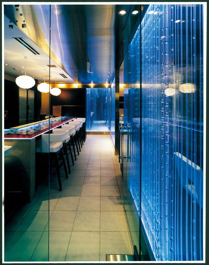 バンコクキッチン  タイ料理(銀座): 銀座コリドー街でもひときわ目立つ、スタイリッシュなタイ料理店。あからさまなタイ風は避けたいというオーナーの意向を反映し、モノトーンで統一。モダンで都会的ななかに各所にアジア的エッセンスを加えた。縦のラインが美しい光のパーテーションはタイのスコールをイメージ。