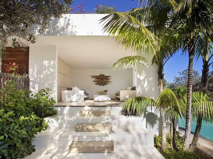 Outdoor lounge: white concrete walls and roof, wooden screen, outdoor couches