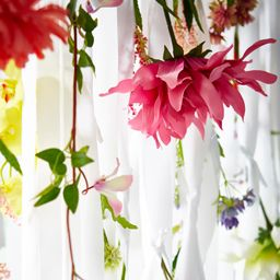 Different artificial flowers hanging in white ribbons.