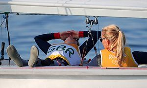 Britain's Hannah Mills and Saskia Clark relax in the Marina Da Gloria after the women's 470 medal race was postponed