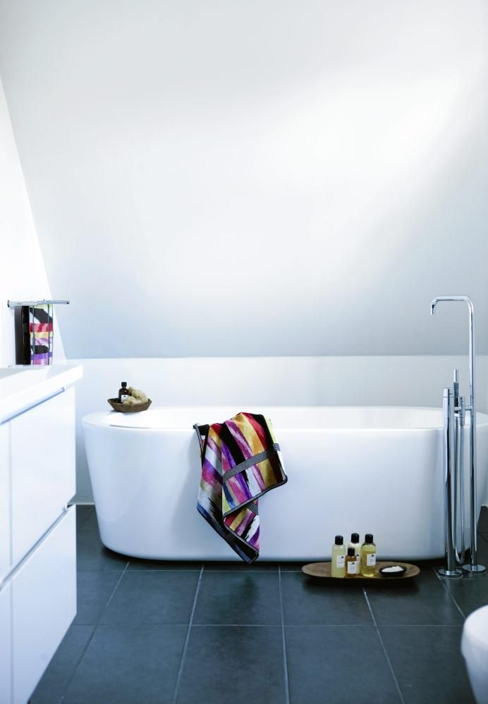 Badekaret er plassert under skråtaket og svever omtrent over det grå gulvet. Legg merke til det stillige armaturet som strekker seg høyt over badekarkanten.