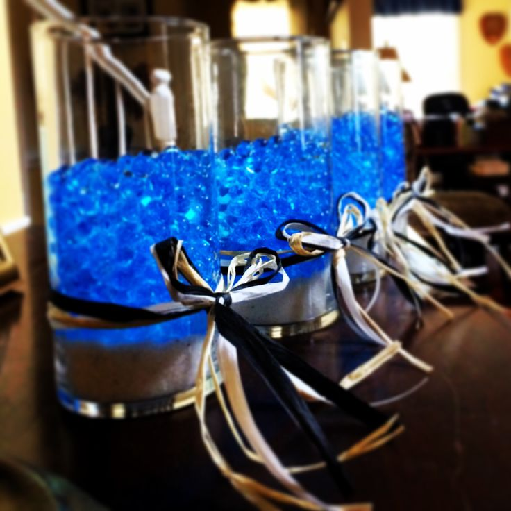 Glowing centerpieces.  Using dehydrated water gems from Michaels, sand,  Dollar Tree vases and submergible LED lights I created a beautiful centerpiece for under $5.00 each!  For this particular event I will be adding blue Glow-sticks instead of any flowers as the event is geared toward our swim team. I incorporated the teams colors (black/white/blue) with the raffia.