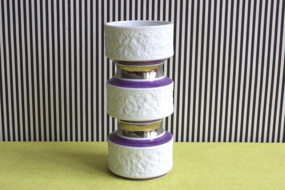 Prachtige vintage porseleinen vaas, gemaakt door Kerafina Royal Beieren KPM in de jaren 70. In witte bisque porselein met een een triple flanged vorm, dit item is afgewerkt met rotsachtige textuur en lila en zilver (spiegel afwerking) hand geschilderde versieringen.  onder uitstekende omstandigheden! Een MUST voor de liefhebbers van de retro :-)  Meten H 7,3(19cm) W 3,35(8cm)  gemarkeerde Roya Porzellan Beieren KPM-635/2