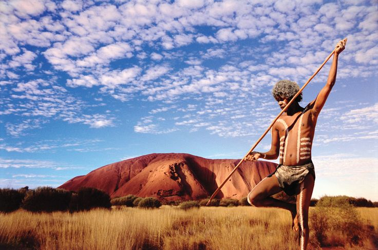 Man standing with Uluru/Ayers Rock in the background, Uluru-Kata Tjuta National Park, southwestern Northern Territory. Grant Faint - The Image Bank/Getty Images
