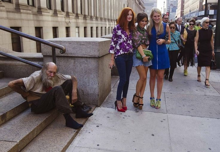 Fashionistas pose for photographs in front of a homeless man outside Moynihan Station following a New York Fashion Week show in September