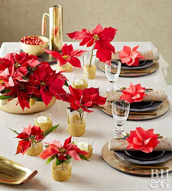 Metallic gold accents and full red poinsettias make for a luxurious traditional Christmas table setting.