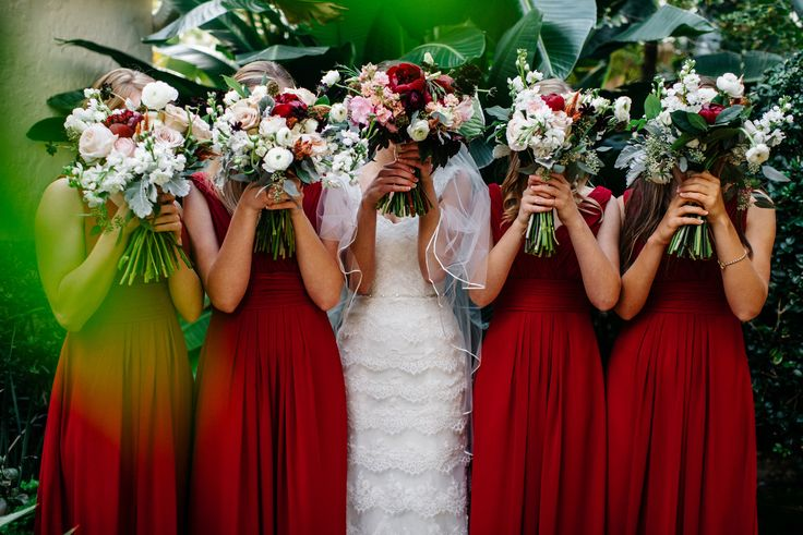 bouquet heads! the bride and her bridesmaids being playful before the ceremony with their bouquets