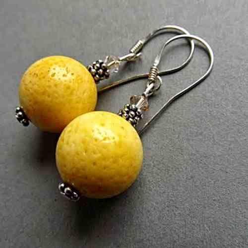 Kolczyki wykonane z kul żółtego korala (16 mm), kryształów Swarovskie bicone (4 mm) w kolorze golden shadow i ozdobnych przekadek, długość kolczyków 6 cm., srebrne otwarte bigle. w KuferArt.pl