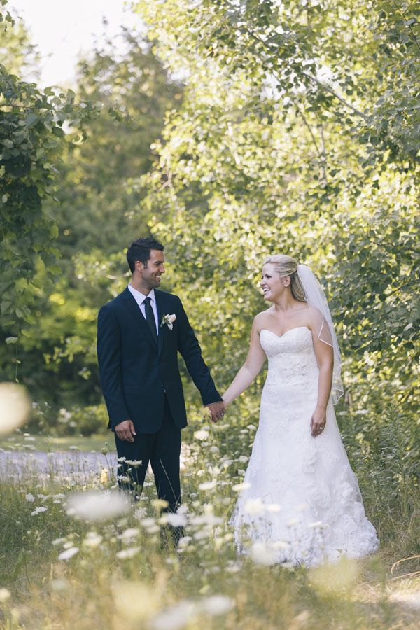 Bride & groom walking in wildflowers. Read their wedding review at The Manor by Peter and Paul's. #sweetheartempirephotography