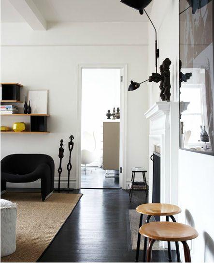black floors, sisal rug, stools, serge mouille light