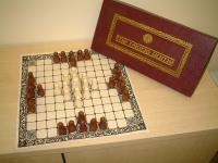 Hnefatafl.  One of the rare breed of games with two unequal sides. The defending side comprises twelve soldiers and a king, who start the game in a cross formation in the center of the board. Their objective is for the king to escape by reaching any of the four corner squares. The attackers comprise 24 soldiers positioned in four groups of 6 around the perimeter of the board. Pieces move like a chess rook.  Derivatives include Breakthru, Break Away, Swords & Shields and Thud.