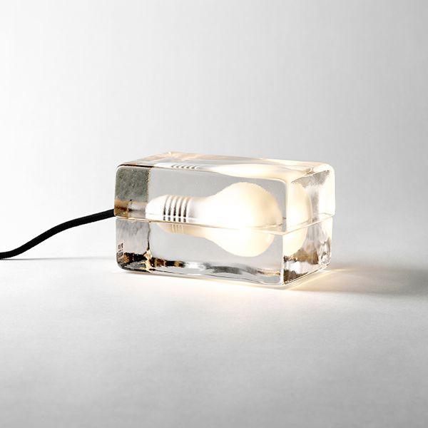 Design House Stockholmin Block-valaisin koostuu kahdesta valetusta lasitiilestä, joiden sisään on hiekkapuhallettu lampun muotoinen syvennys. Valonlähde liitetään tekstiilipäällysteiseen virtajohtoon ja asetetaan tiilien väliin.