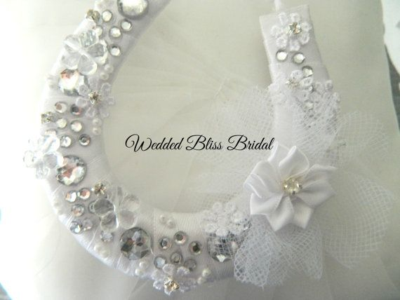 Classic White satin bound horseshoe keepsake to wish the Bride and groom all the Luck of the wedding day , as tradition goes the horseshoe prongs facing in the upwards position will capture the luck . Beautifully embellished with beads , Flower motif with a touch of diamante bling .