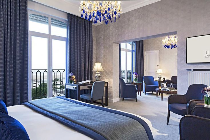 Luma chairs in Blue from Sandler Seating. Upholstered armchairs and lounge chairs with a solid wood frame at a bedroom in Hotel Barriere L'Hermitage, France.
