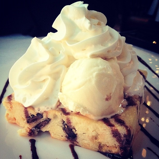 Moxie's White Chocolate Brownie. Rich chunks of white and dark chocolate in a fresh baked brownie, topped with whipped cream, vanilla ice-cream and chocolate sauce! #dessert #brownie