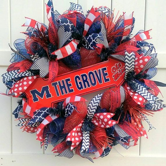Calling all Ole Miss Football fans! The historic spot for Ole Miss tailgating - The Grove! This is a handmade deco mesh wreath with a metal arrow displaying The Grove. The wreath is made with two different designs of deco mesh: classic red and yale blue. It is adorned with six different ribbons in crimson and blue. This wreath is made on a 24 inch work wreath. It measures slightly larger, about 25 in diameter. Perfect gift for any Ole Miss fan or high school senior who plans to attend the…