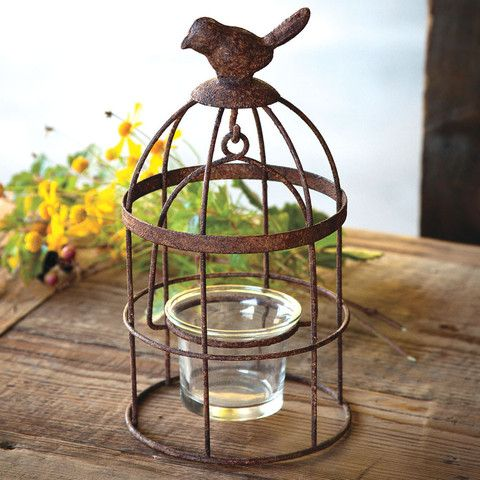 A small songbird sits atop a rustic cage for the perfect whimsical decor! The…