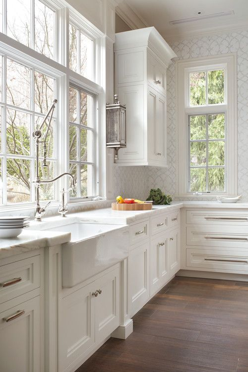 Love the brightness,  tall windows, wall paper and cabinets! Pretty hardware.