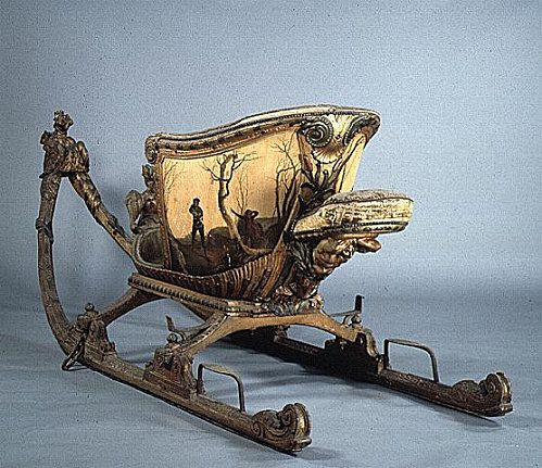Sled dating from around 1720. Preserved museum of carriages Versailles     This wooden box painted with patterns and winter landscape is decorated with a sculpture of a chimera, and interior trim are triton. The silk velvet is green-yellow.