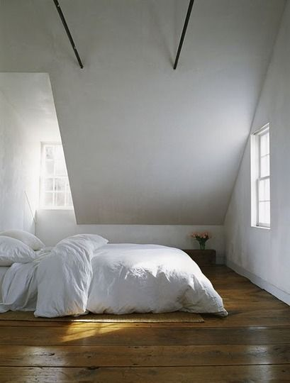 Gorgeous floors, thick white comforter, and a vase of flowers - beautiful minimalist bedroom!