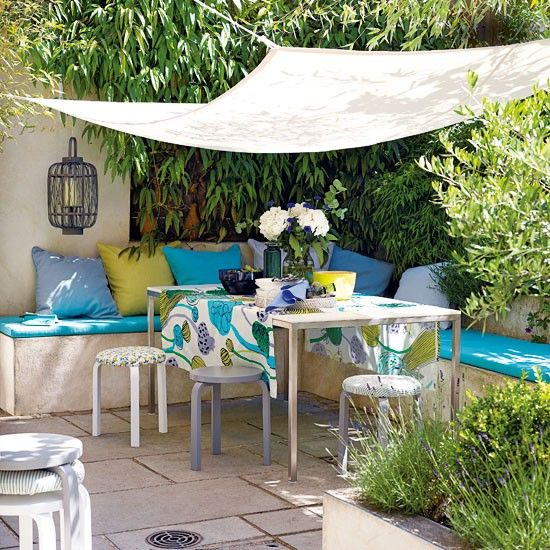 Relaxed summer terrace. Banquette seating with removable cushions, canvas canopy as a parasol alternative, and stacking stools instead of bulkier chairs all makes for easier winter storage.