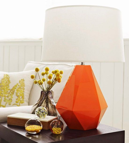 Home Decorating Tips - Graphic Variety: Fill the relatively small space on a side table in the living room with a few well-chosen pieces. Vary their size and shape for visual interest. Here, a unique and colorful lamp is a sculptural focal point next to round paperweights, a rectangular box, and a glass pitcher of flowers.