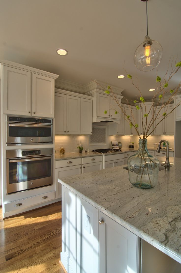 Horizon Custom Builders beautiful kitchen with white cabinets gray island and subway tile backsplash in this Parade Home winner