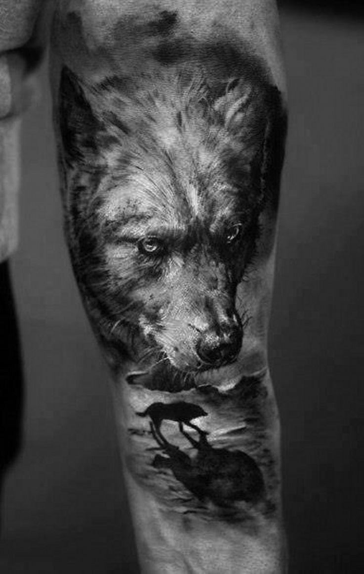 Super realistic dark wolf with silhouette of a wolf forearm tattoo