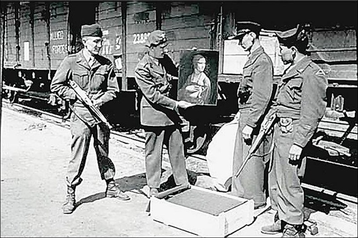 The 'Monuments Men' changed history by returning art to the rightful owners. Military personnel, including two unidentified American GIs, admire one of Leonardo da Vinci s masterpieces, Lady with an Ermine, before its return to Cracow, Poland in this 1946 photo. The painting had been stolen by Nazi officers from the Czartoryski Museum in Kracow upon the German invasion in 1939