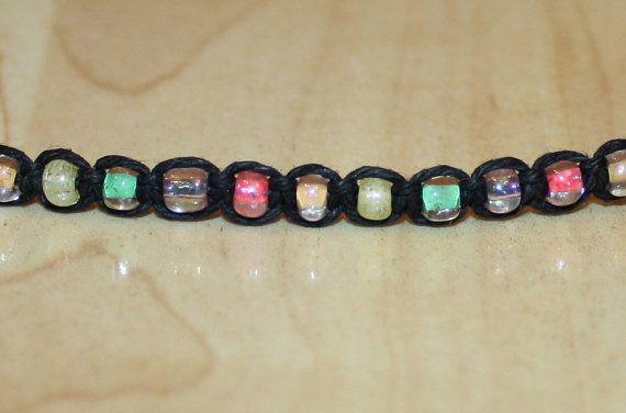 Este cáñamo cáñamo moldeada a mano gargantilla collar negro de características en un nudo cuadrado tejido con un patrón repetitivo de tutti frutti arco iris cristal granos de la semilla (rosa, naranja, amarillo, verde, púrpura) y un cierre de bucle botón rosado. Longitud de gargantilla: Seleccione un tamaño de la lista desplegable ** Tamaño más popular de las mujeres es de 14 ** Corresponde a la longitud de la sección de tejido/cuentas de nudo a nudo, excepto el cierre botón loop. ** Si...